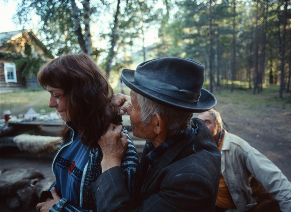 Inhaling and blowing cedar-bark smoke, a shaman asks the spirits to banish disease and ailments.