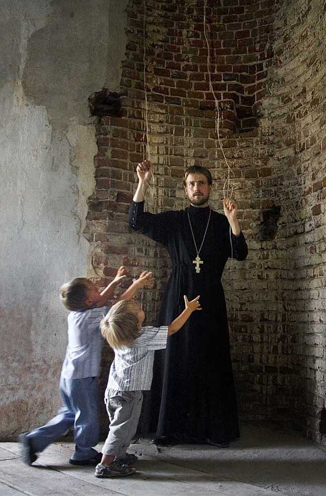 Le prêtre Sergueï Smirnov dans l'une des églises rurales de la région de Voronej. Ses fils accourent au son des cloches de l'église. Ecolier et étudiant en économie, le père Sergueï a souvent visité des monastères avec son père. Ces voyages, ainsi que le contact qu'il a eu avec les moines, a influencé la décision de Sergueï d'entrer au Séminaire théologique orthodoxe de Voronej après l'obtention de son diplôme. Il est actuellement membre du clergé du diocèse de Voronej.