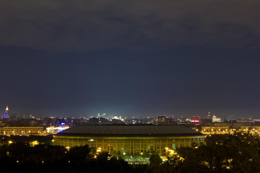 """OLYMPIASTADION LUSCHNIKI. Russlands größtes und berühmtestes Stadion ist das Luschniki in Moskau. Insgesamt bietet es 89.318 Plätze. Es gehört zum Olympiakomplex und hieß früher """"Zentralstadion namens W. I. Lenin"""". Der Name Luschniki stammt von den überschwemmungswiesen in der Biegung des Flusses Moskwa, auf denen das Stadium errichtet wurde, und bedeutet übersetzt etwa """"Die Auen""""."""