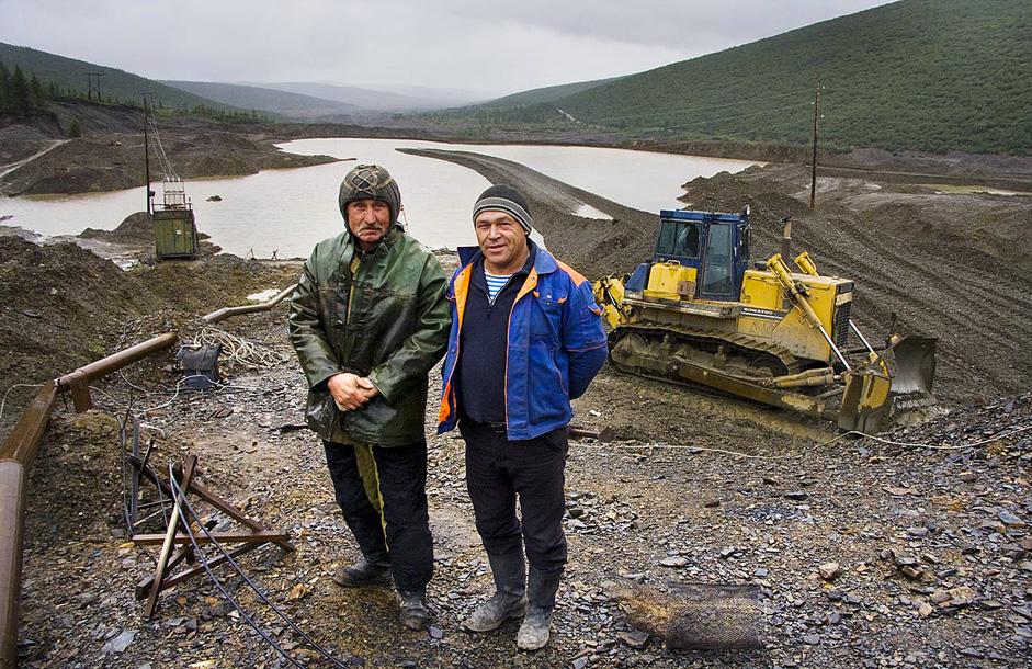 ロシアの主要な金採掘地域の一つがコルィマ鉱山だ。典型的なコルィマ鉱山の景色を背景にした金採掘者。含金石を洗い、金を選別する洗浄機には、貯水池からパイプを通じて水が送られる。