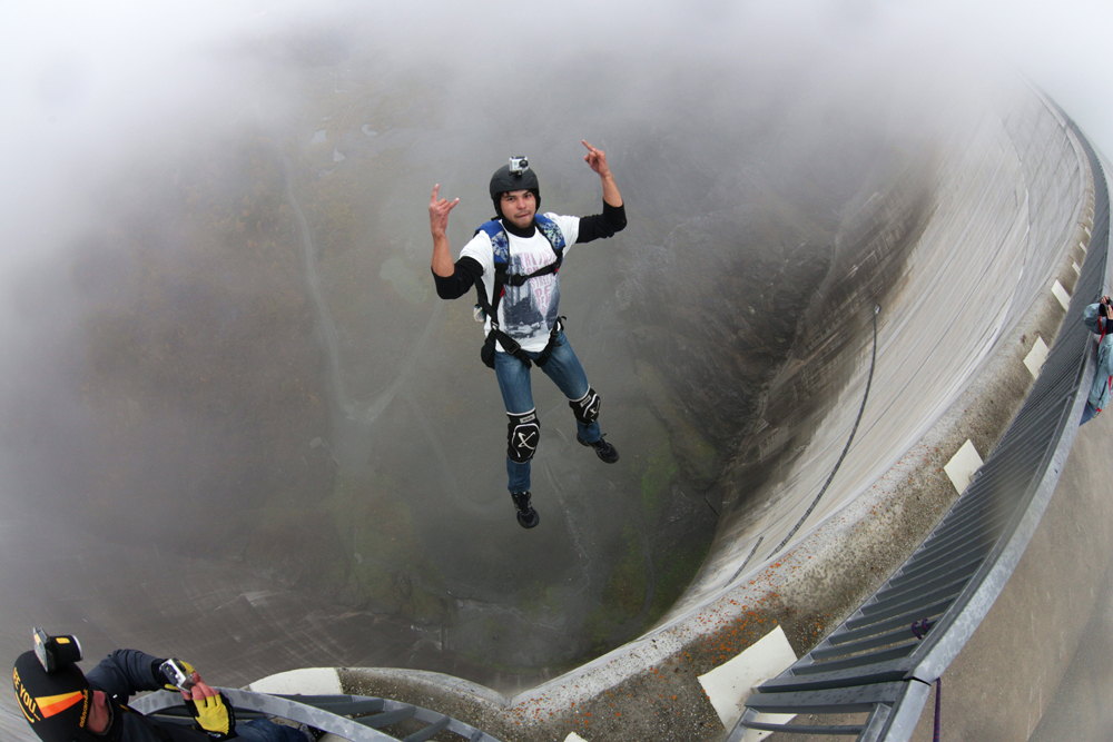 Skydivers use the air flow to stabilize their position, allowing the parachute to deploy cleanly. BASE jumpers, falling at lower speeds, have less aerodynamic control, and may tumble.