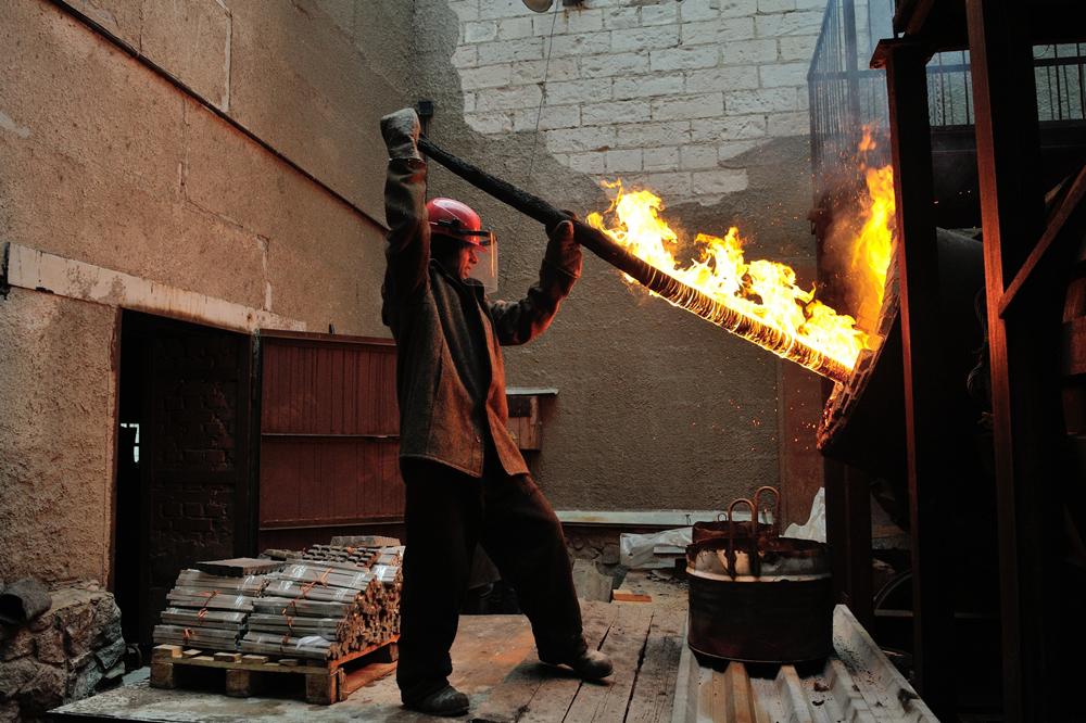 炉内温度は1200℃近い。布スーツの製錬師は、長い丸太で時折「醸造」をかき混ぜる。丸太は、彼の目の前で黒焦げになる。