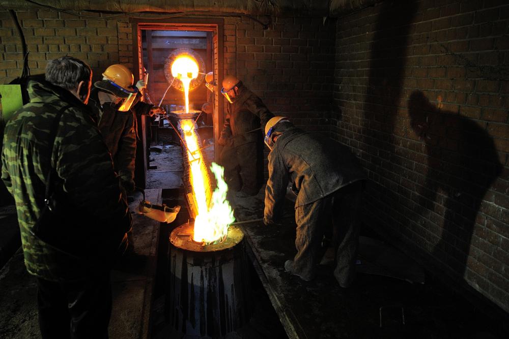 液体金属は最初はちょろちょろと金型の黒い開口部に流れ込み、火の小川のように、流れ込む。