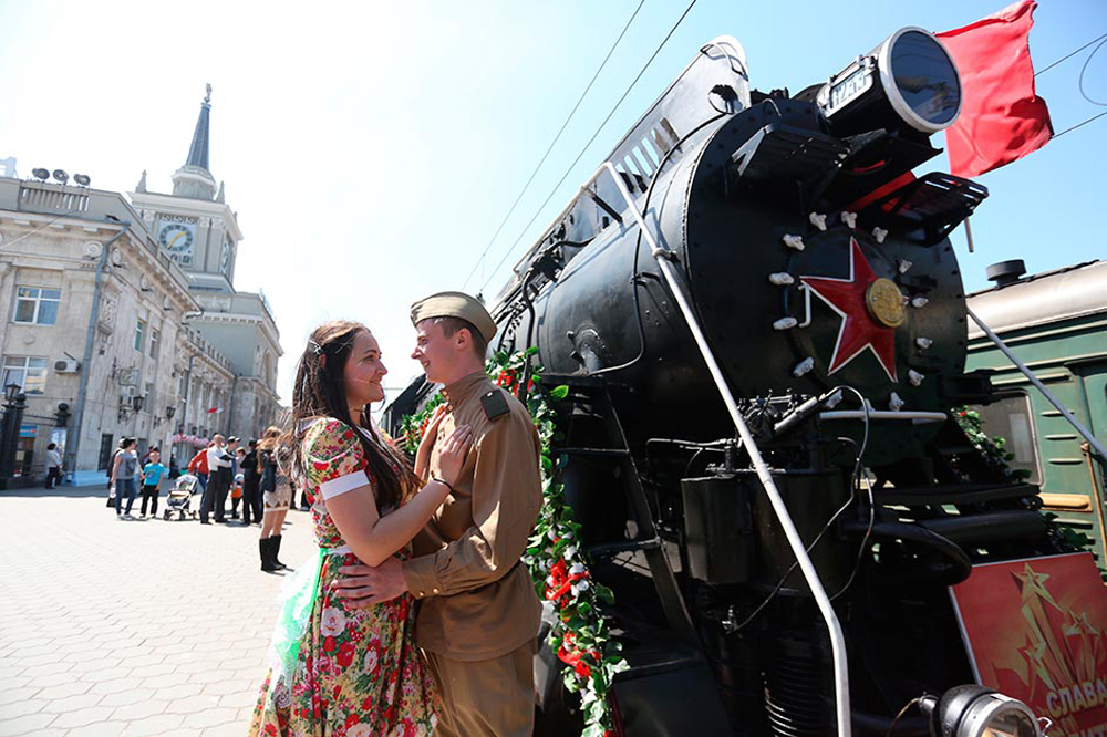 """Young people wearing war-time clothes stand at the retro train """"Victory"""" that has arrived at Volgograd railway terminal to mark the 70th anniversary of the Battle of Stalingrad."""