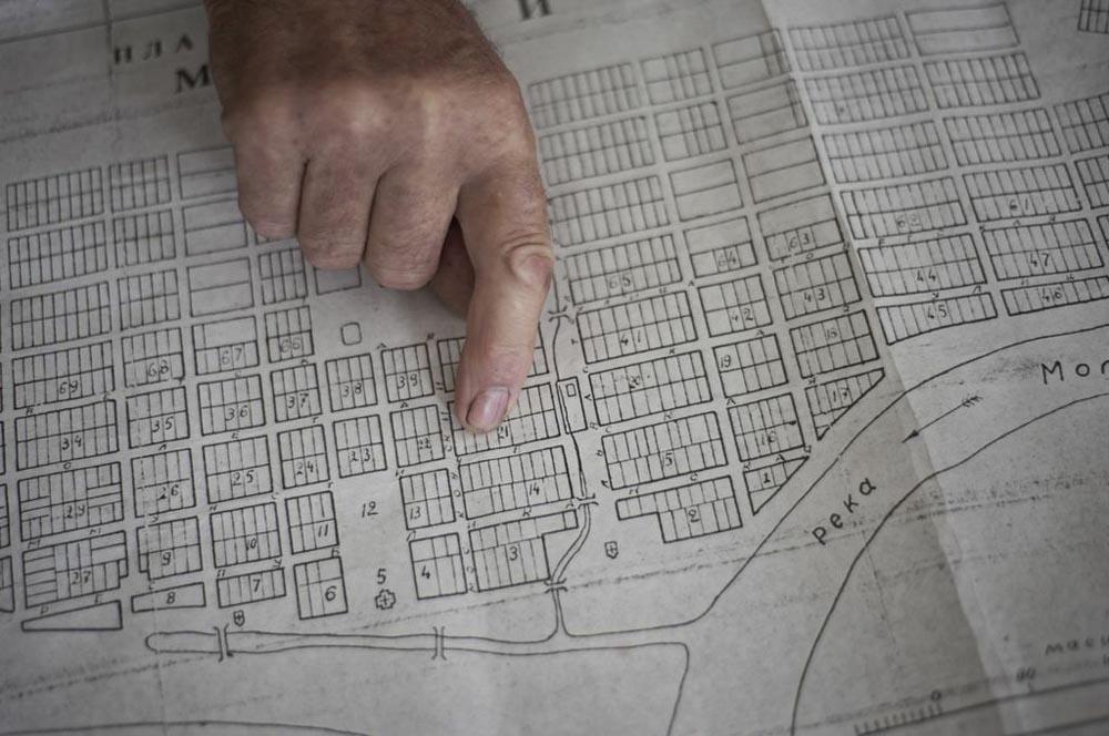 Николај Новотељнов ја покажува Молога на картата. Неговото семејство живеело на парцелата број 21.