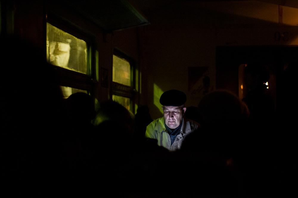 電灯の消えた車両でディスプレイを見る男性。