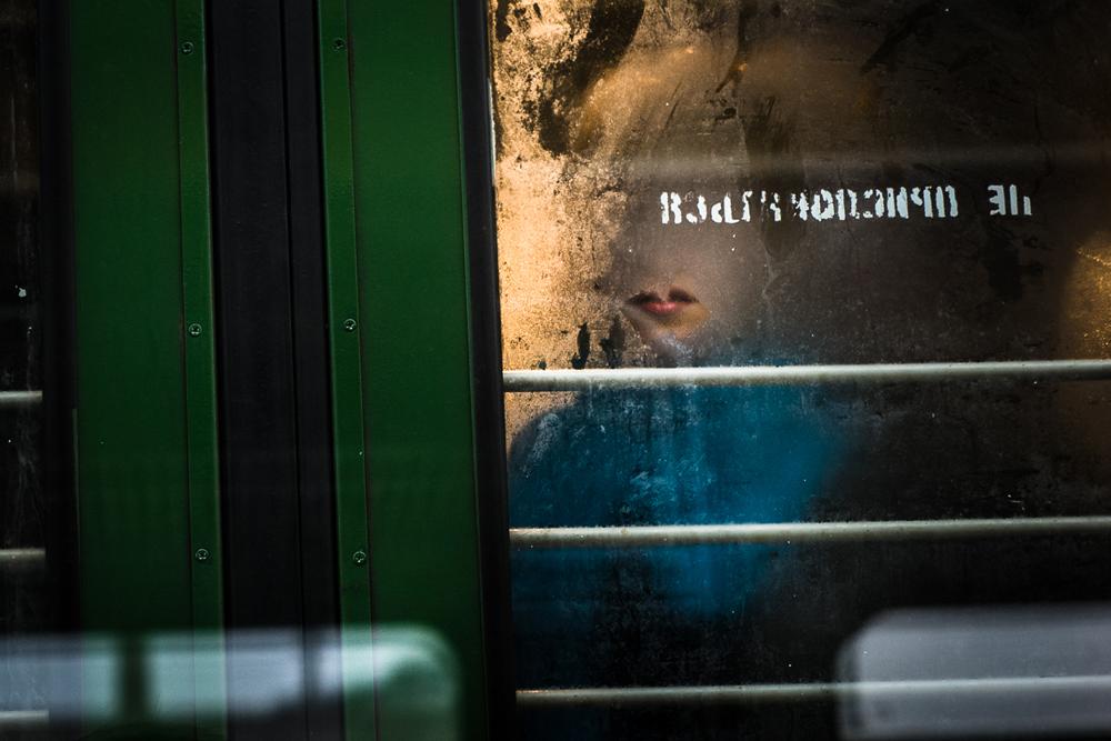 電車のガラスドアの後ろの女性。ラッシュアワーの電車は満員で、多くの乗客が立っている。車両内が窮屈で酸欠気味なため、車両間の通路にも多くの人がい る。ラッシュアワーには約30人が待合室にいる。