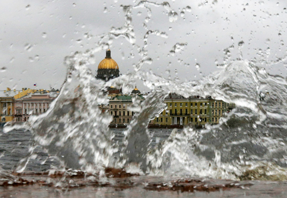 The domes of St. Isaac's Cathedral and residential and office buildings are seen through waves during strong storm winds and rain in central St. Petersburg.