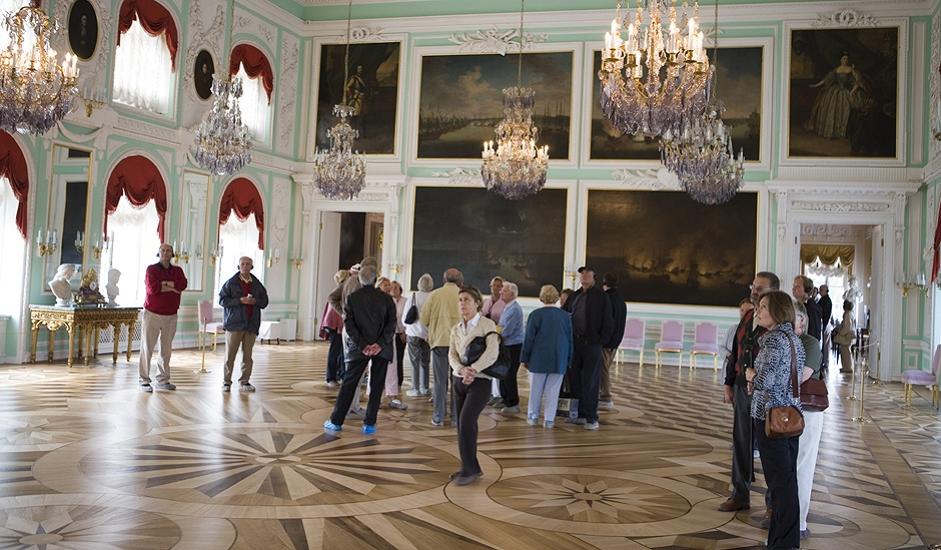 """Dvorac su okupirali nacisti u Drugom svjetskom ratu istovremeno s blokadom Lenjingrada, i tada je Peterhof vandaliziran i opljačkan. Ovdašnji stručnjaci s pravom su ponosni na njegovu uspješnu poslijeratnu rekonstrukciju, učinjenu uz mnogo napora. Pri obilasku obratite posebnu pozornost na """"Prijestolničku sobu"""", s veličanstvenim osvjetljenjem i portretima Romanovih, obližnju sobu za dvorske dame, kao i zanimljive drvene podove u """"Zapadnoj kineskoj radnoj sobi""""."""