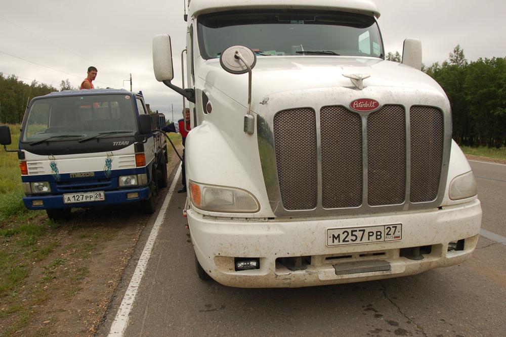 Vozač kamiona puni rezervoar svog vozila (na slici). Vozači su ekonomični glede svega, uključujući i gorivo. Često kupuju od lokalnog seoskog stanovništva koje gorivo naplaćuje 1,5-2 puta jeftinije od benzinskih postaja.