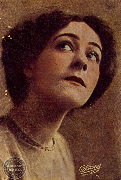 アーラ・ナジモワ(本名ミリアム・レヴィントン、1879 -1945)、世界の無声映画でもっとも人気があり、目立つ女優の一人、プロデューサー、脚本家。17歳でモスクワに行き、創設間もないモスクワ芸術座で 演技を始める。徐々に成功し、世界中で公演し始める。1905年、夫のパーヴェル・オルレネフとロシアから亡命。1916年、プロデューサーのルイス・セルズニックから、映画「戦時花嫁」への出演を依頼される。映画制作会社「メトロ」は、1週間1万3000ドルの契約をナジモワと結んだ。このようにして、 アメリカでもっとも高額な映画スターになった。メアリー・ピックフォードですらこれより少なかった。数十作品に出演し、ハリウッド・ウォーク・オブ・ フェームでは、2つの星でアメリカの芸術界への功労が記されている。
