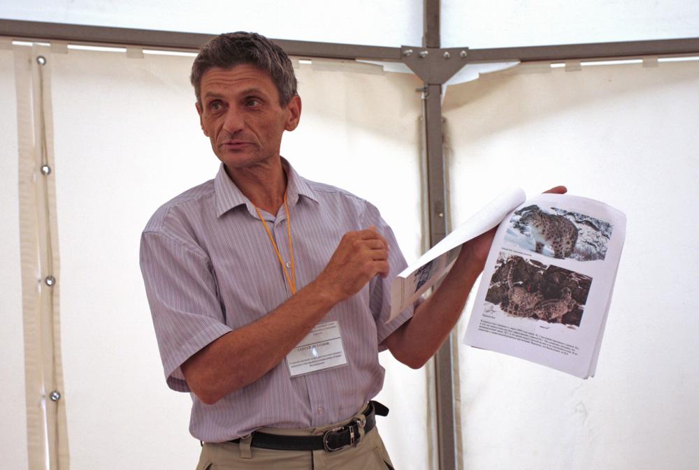 """Отворањето на центарот за посетители беше темпирано да се совпадне со тридневниот семинар за ретките видови на животни. На фотографијата е еден од учесниците, Сергеј Истомов, вработен во одделот за наука. Тој држи пасош за снежниот леопард. Секое животно """"фатено"""" од страна на камерата има таков пасош."""