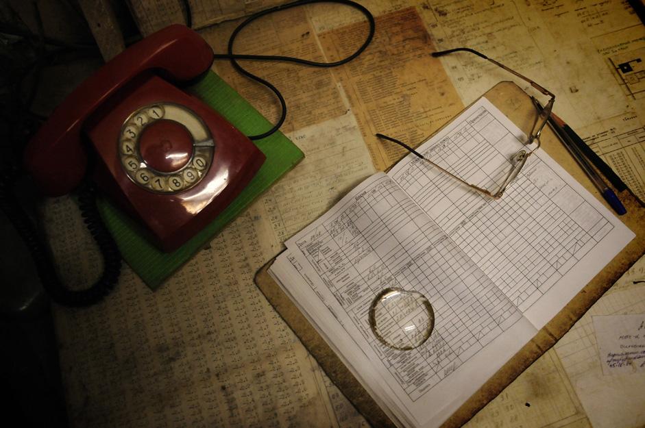 気象観測所の机上にある古めかしい電話。数年前、電話線のつながり具合が悪くなり、通信速度のより遅い、昔風のダイヤル電話し か使用できなくなった。最近使用されているのは新しいボタン式の電話で、水文気象サービスの本部までは衛星通信を使ってデータを送信するようになった。