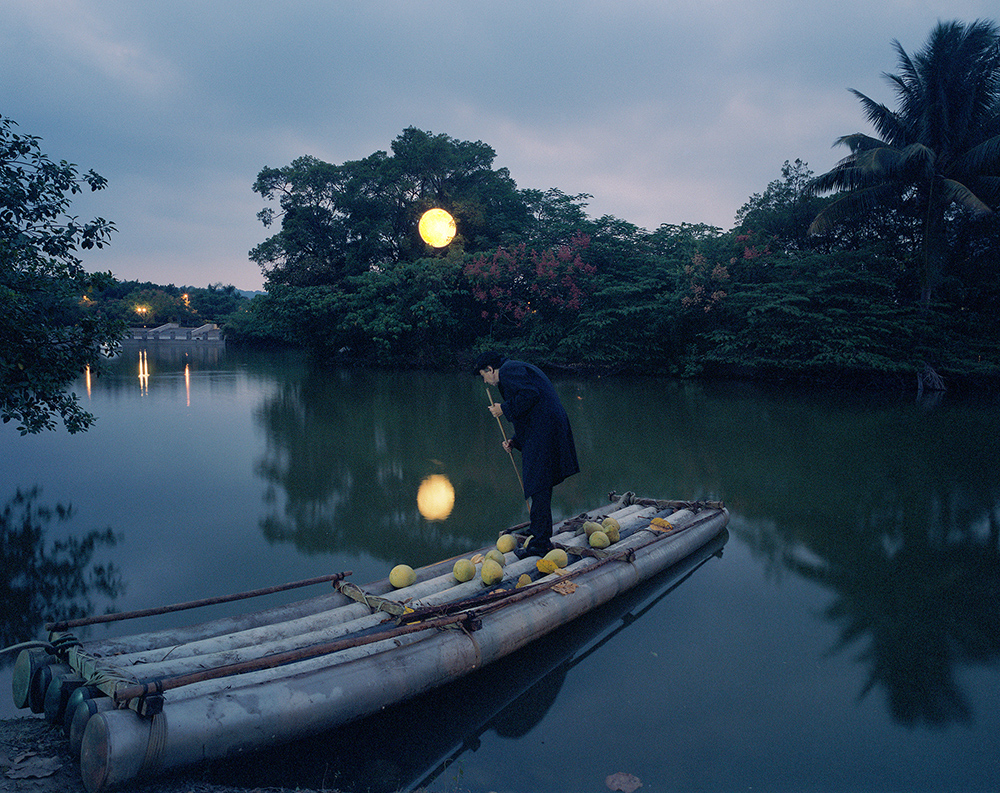 "To top all, Leonid Tishkov opened an installation entitled ""Yellow Moon"" at the Kaohsiung Museum of Fine Arts. Time passed and the moon grew into a full moon. The artist is setting off on an old, bamboo raft similar to Odysseus, following the moonlight. / Full yellow Moon in Museum's park"