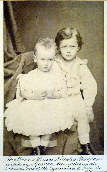 According to historic evidence, the Romanov children were raised in a very strict household. They slept in army beds, woke up at 6 am, and lived and slept in simply-decorated rooms. Only the icon was ornately decorated. / Nikolai and his brother, Grigory (on the left)