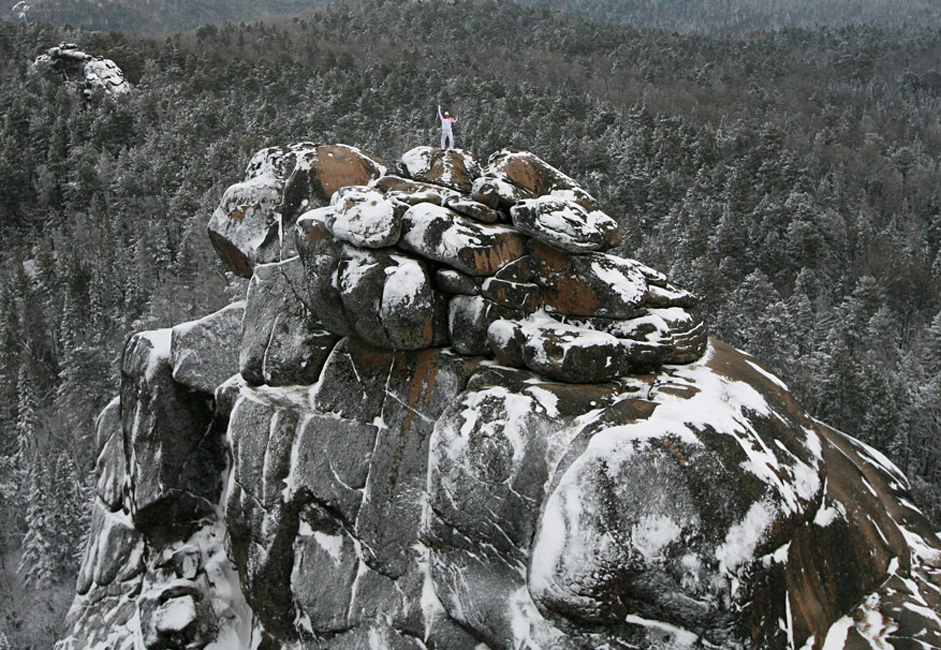 """Russian alpinist Vladimir Gunko stands at the top of the rock named """"The First Stolb"""" (the First Pillar) at the Stolby national nature reserve during the Sochi 2014 Winter Olympic torch relay in the Siberian Taiga area outside Krasnoyarsk."""