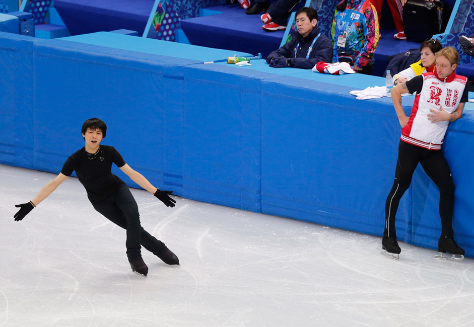 Yuzuru Hanyu of Japan (L) skates as Evgeni Plushenko of Russia (R) looks on during a figure skating training session in preparation for the 2014 Sochi Winter Olympics, in Sochi.