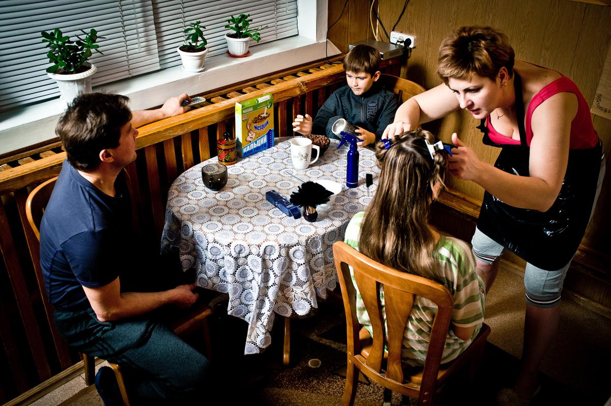自宅で長女の髪を切るレーナさん。//彼女の家族は、娘の(近隣の大きな居住区でネイリストの仕事をしている)ティンダさん、息子(小学生)と夫のイーゴリ・プチョルキンさん(ロシア鉄道に勤務)だ。