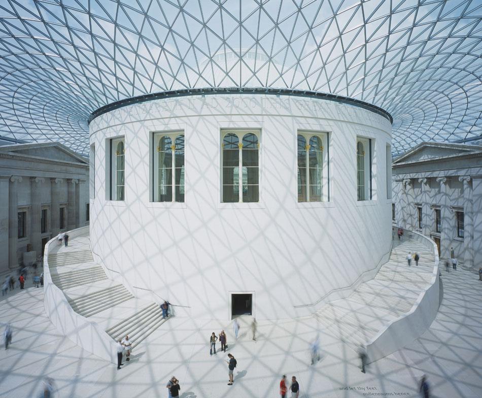 シューホフが開発した格子状の建築物には、吊り構造の骨組みもあった。通常の金属のけたを使わないため、透かしたメッシュが見物者の頭上高くまでそびえ立つ。シューホフを自分の「グル」(訳注:精神的指導者)だと言う有名な建築家のノーマン・フォスターは、シューホフのアイディアを大英博物館の屋根を造る時に使った。//大英博物館、ロンドン、イギリス