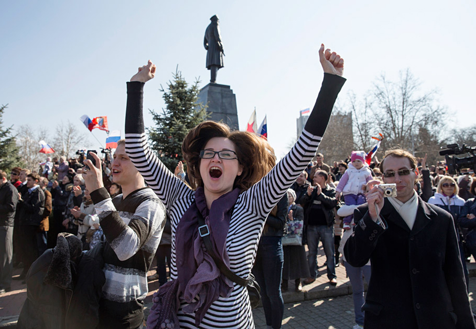 A woman jumps for joy during a broadcast of Russian President Vladimir Putin's address to the Federal Assembly in Sevastopol March 18, 2014. Putin, defying Ukrainian protests and Western sanctions, on Tuesday signed a treaty making Crimea part Russia but said he did not plan to seize any other regions of Ukraine.
