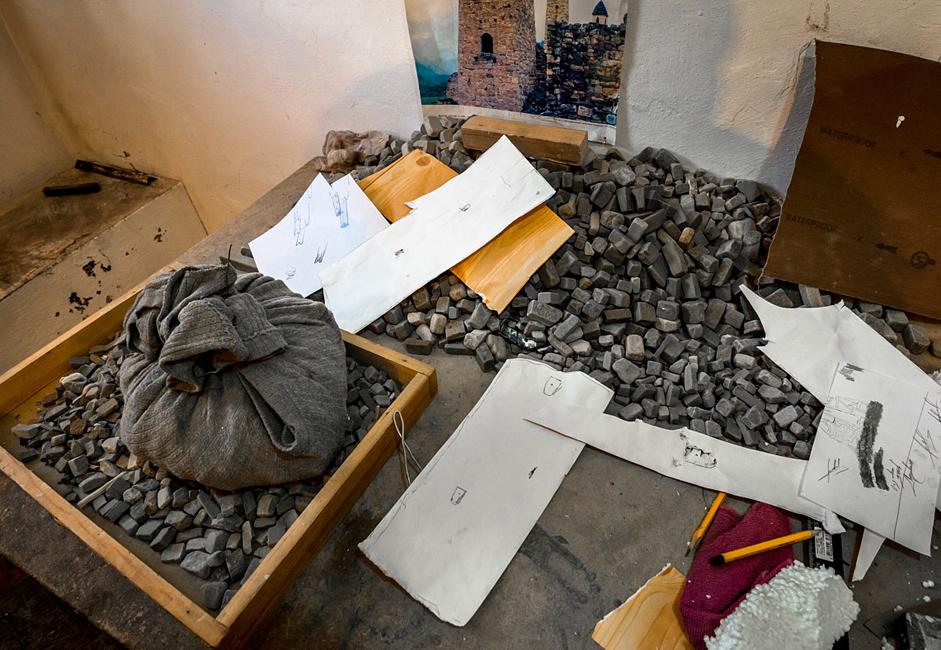 気泡ゴムは接着剤を使ってつけられた小石で覆われる。 マゴメド=バシールさんがモデルの製作に使用するすべての材料は自然のものだ。小石は、モデルに再現する地域のものを彼が取りに行っている。