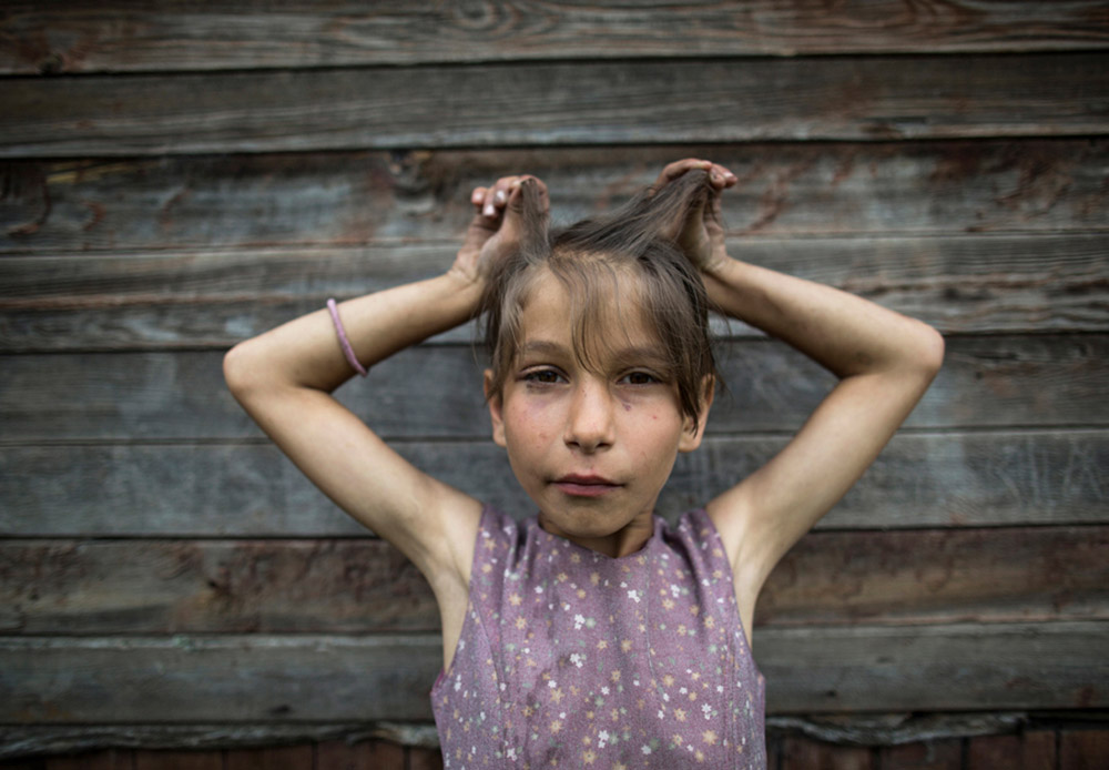 "Pada musim panas 2013, fotografer asal Amerika Louisa Marie Summer menyusuri Jalan Raya Federal Amur (Amur M58) sepanjang 2.165 kilometer. Ia mengendarai mobil dari Chita ke Khabarovsk, Siberia Tenggara selama tujuh hari. Sepanjang perjalanan ia memotret para penduduk desa dari berbagai suku dan kelas. Summer berusaha menangkap gambaran personal, ekonomi, sosial mereka. Kehidupan para penduduk yang tinggal di sisi jalan tersebut sungguh tenang dan sederhana. ""Aku berjumpa dengan gadis kecil bernama Dasha di depan rumahnya di Mogocha, Kawasan Trans-Baikal. Ketika pertama kali Dasha melihatku, ia berlari masuk ke rumah lalu keluar lagi. Ia tampak penasaran, dan dengan riasan ceria ia mulai berpose di depan kamera,"" cerita Summer."