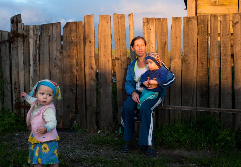 Seorang ibu dengan dua anaknya di depan rumah mereka di Chernyshevsk, pusat pemerintahan wilayah Chernyshevsky, 300 kilometer di sebelah timur laut Chita. Di desa kecil di samping jalan ini, seorang penduduk lokal bernama Vladimir mengelola sebuah penginapan kecil. Awalnya ia membuka penginapan karena ada dua pengemudi truk mencari tempat menginap saat truk mereka rusak.