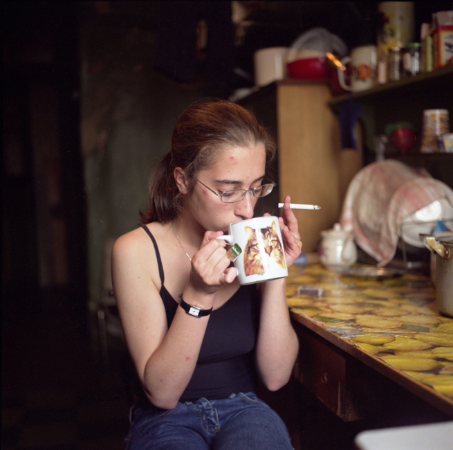Karina, an architecture student, has tea in a neighbor's kitchen. She was born in and has always lived in this communal apartment in central St. Petersburg. She likes the sense of community here and would not want to move out.