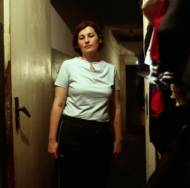 Marina, a nurse and a divorced mother of one son, poses for a picture in the corridor of her communal apartment. She says her everyday reality at home includes struggling with neighbors over utility bills and other conflicts. For example, one neighbor is an alcoholic who permanently hosts parties for his drunk friends. Marina says her modest income does not allow her the opportunity to leave this place.