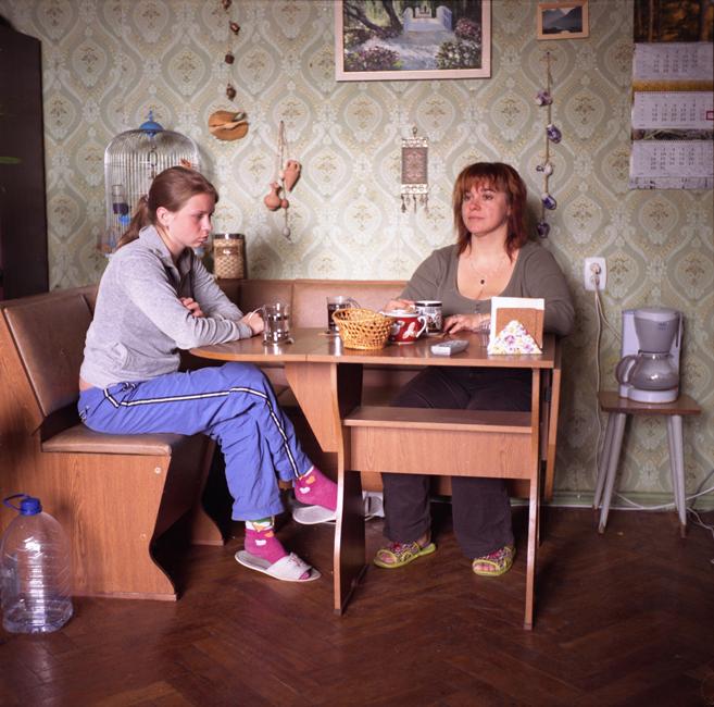 Marina (lijevo), agentica za nekretnine, doručkuje sa svojom kćeri Arinom. Marina i dvoje od njezino troje djece dijele sobu od 30 m² kamo su doselili mjesec dana prije nego što je slikana ova slika, nakon što se Marina razvela od muža. Većina Rusa odabire kuhinju ili blagovaonicu za ručanje, no stanovnici komunalki nemaju taj luksuz pa jedu u svojim sobama.