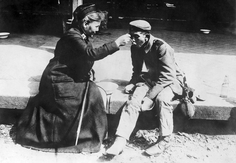 Une infirmière de la Croix Rouge française aide un mendiant, Allemagne, 1914-1918.
