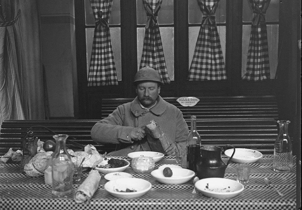 Un militaire en permission dîne dans la cantine militaire de la Gare de l'Est, Jacques Moreau. Paris, janvier 1917.