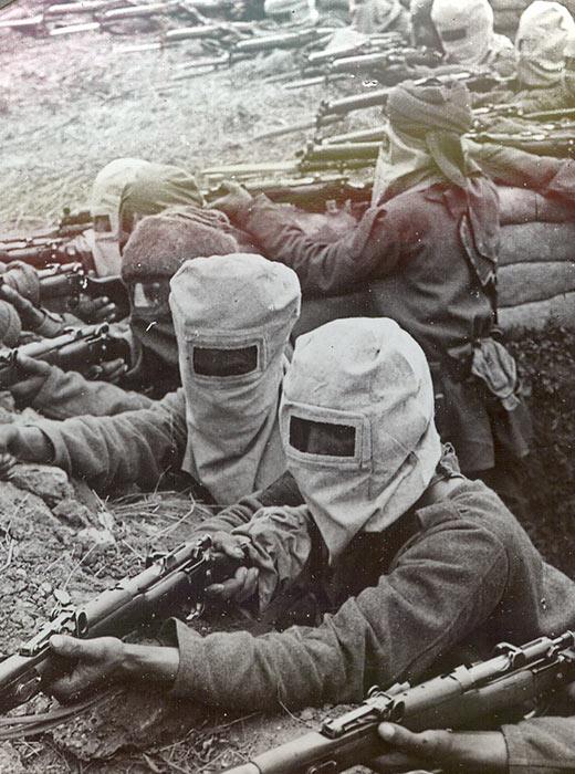 """Infanterie équipée de masques à gaz à haute pression tire sur les ennemis battant en retraite après avoir pris la tranchée """"Hun""""."""