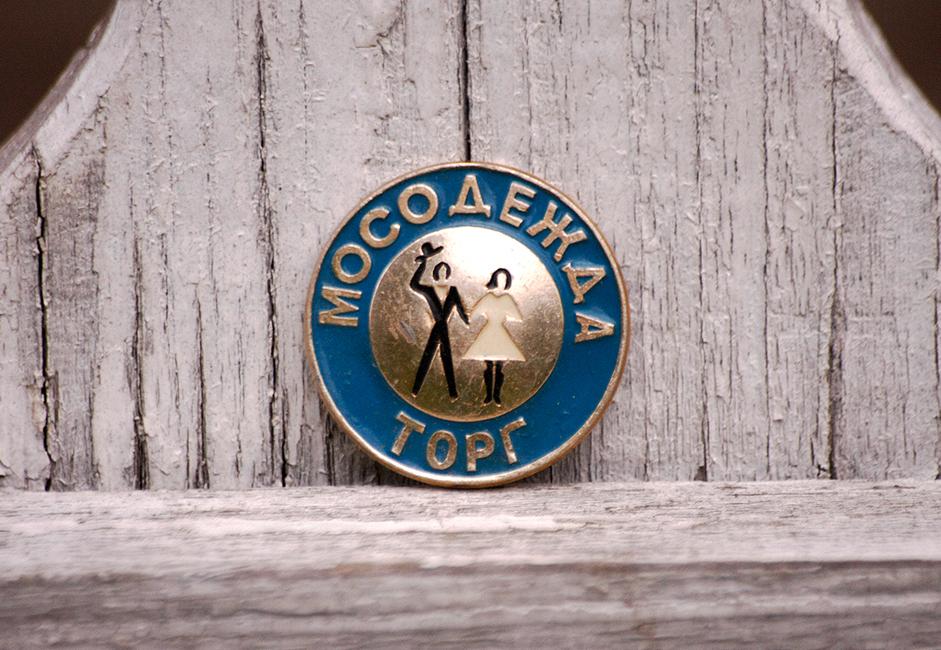 Radna značka za zaposlenike u modnoj trgovini u Sovjetskom Savezu. Prodavači u velikim robnim kućama poput GUM-a i CUM-a uglavnom su nosili ovakve značke.
