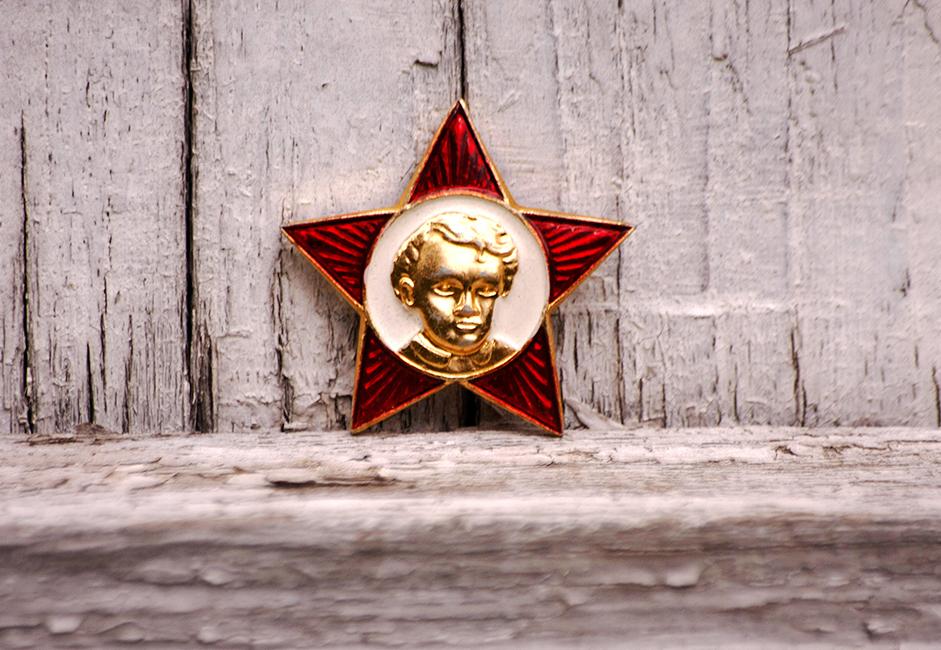 """Posljednje izdanje Oktobarske zvijezde. Proizvodila se do 1991. Oktobarska organizacija osnovana je 1923. U početku su njezine članove činila djeca sudionika Oktobarske revolucije iz 1917. Otuda naziv """"Oktjabrata"""" ili Djeca Oktobra. Kasnije su se samo djeca od 7 do 9 godina nazivala Djecom Oktobra."""