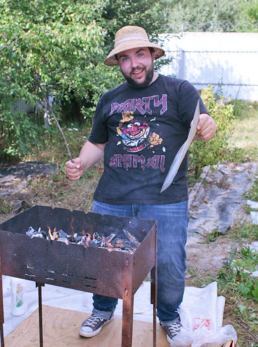 """Piotr, 25 ans. Il est sur le point de faire cuire des chachliks (brochettes). C'est précisément pourquoi il porte un t-shirt vintage de soirée. Le message """"Party animal"""" est mérité."""