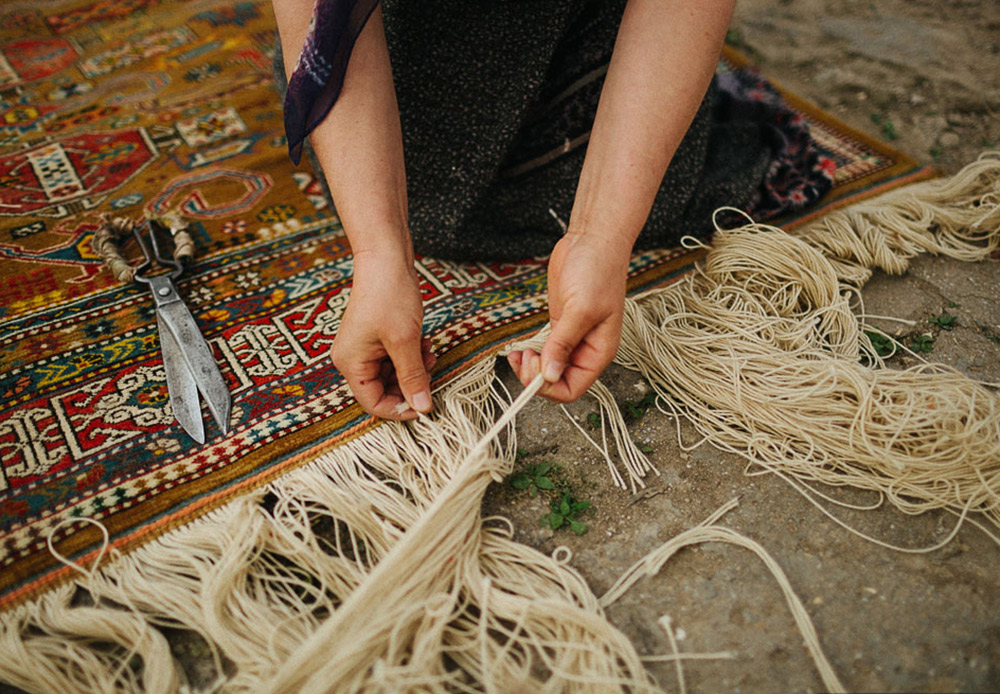 The women have finished their work. After one of them has cut the main threads, they ceremoniously take their beautiful rug into the courtyard.