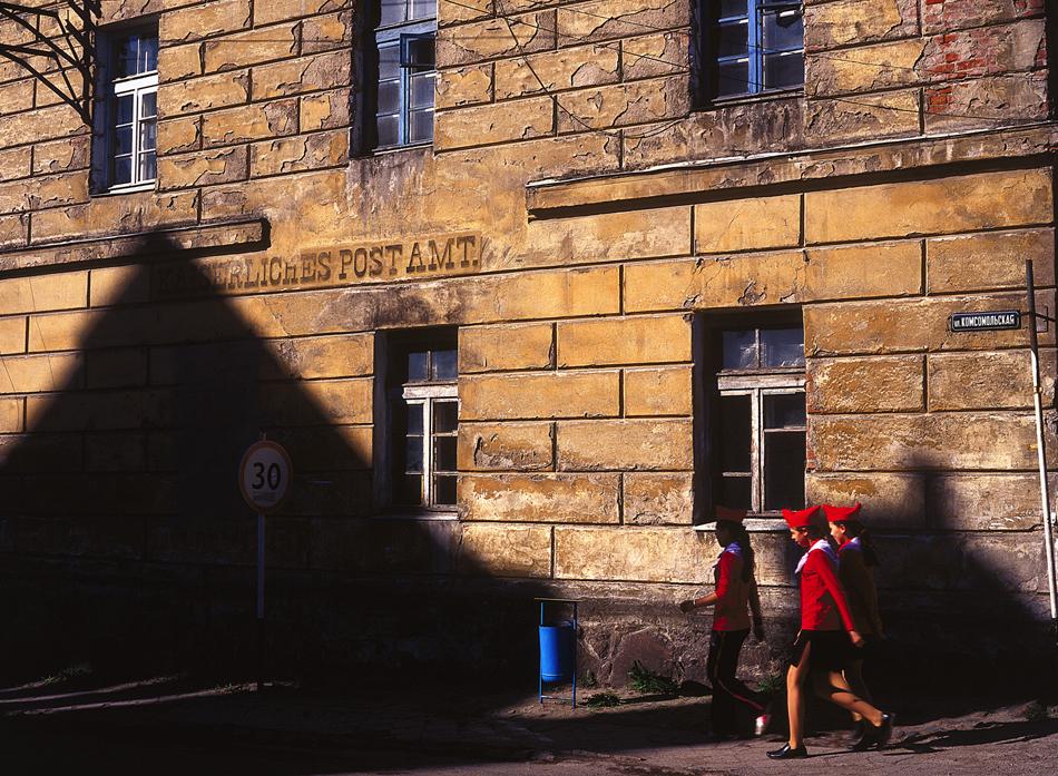 """Пионерчета край сграда, на която все още се чете надпис на немски: """"Императорска поща"""", Озьорск. / Британските и руските бомбардировки през 1945 г. оставят непокътнати едва 20% от Кьонигсберг и разрушават не само стените, но и историята на града. След толкова много години за някои жители 1945 г. е началото на града, а за други – неговият край."""