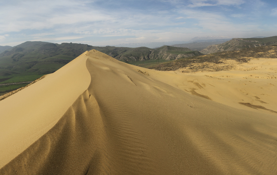 The Sarykum Dune in Dagestan is situated near the regional capital of Makhachkala. Russian scientists consider Eurasia's largest sand dune to be a relict dune, meaning it hasn't undergone changes like the geological structures surrounding it. The dune's tallest point is 250 meters high. The mound is made up of fine golden sand and resembles a miniature Asian desert.
