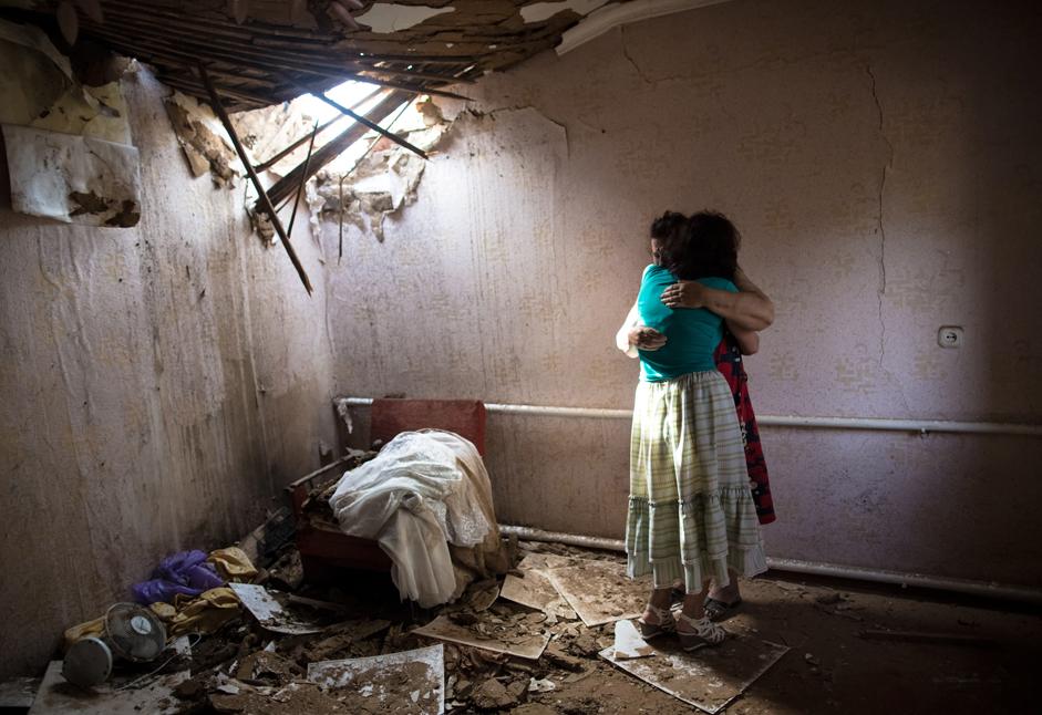 スラヴャンスク郊外で夜間に繰り広げられた砲撃により破壊された自宅にいる女性たち。 2014年