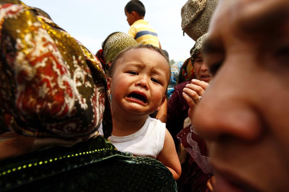 キルギスのオシ市から数キロ離れたウズベキスタンの国境を越えて、集団で逃れる子連れの避難民たち。 2010年