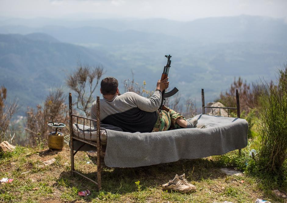 Sirski vojak leži na postelji na pregledni višini nad mestom Kessab, 2014.