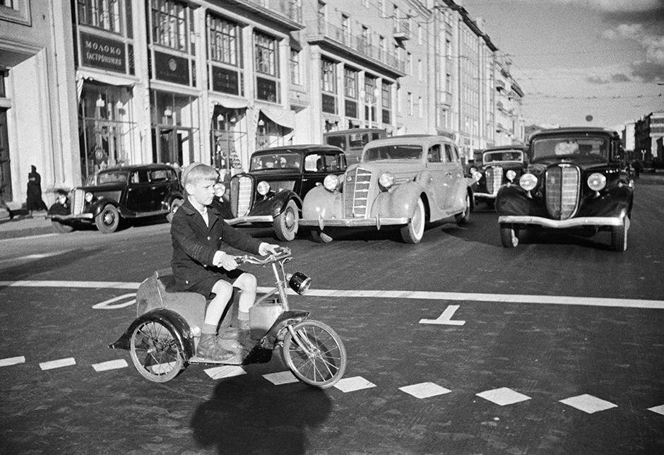 家族全員が彼を手伝い、写真を洗い、ガラスに並べ、グロスで仕上げ、出来上がった写真を切った。息子のアナトリーが修正をした。// ゴーリキー通りを自転車で渡る少年。モスクワ、1935年