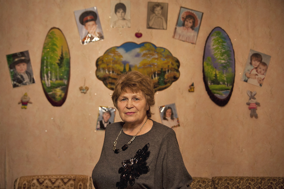 The wall that serves as a background for her portrait marvelously reflects the values of the rural teacher: Russian nature and photographs of her daughter and grandchildren.