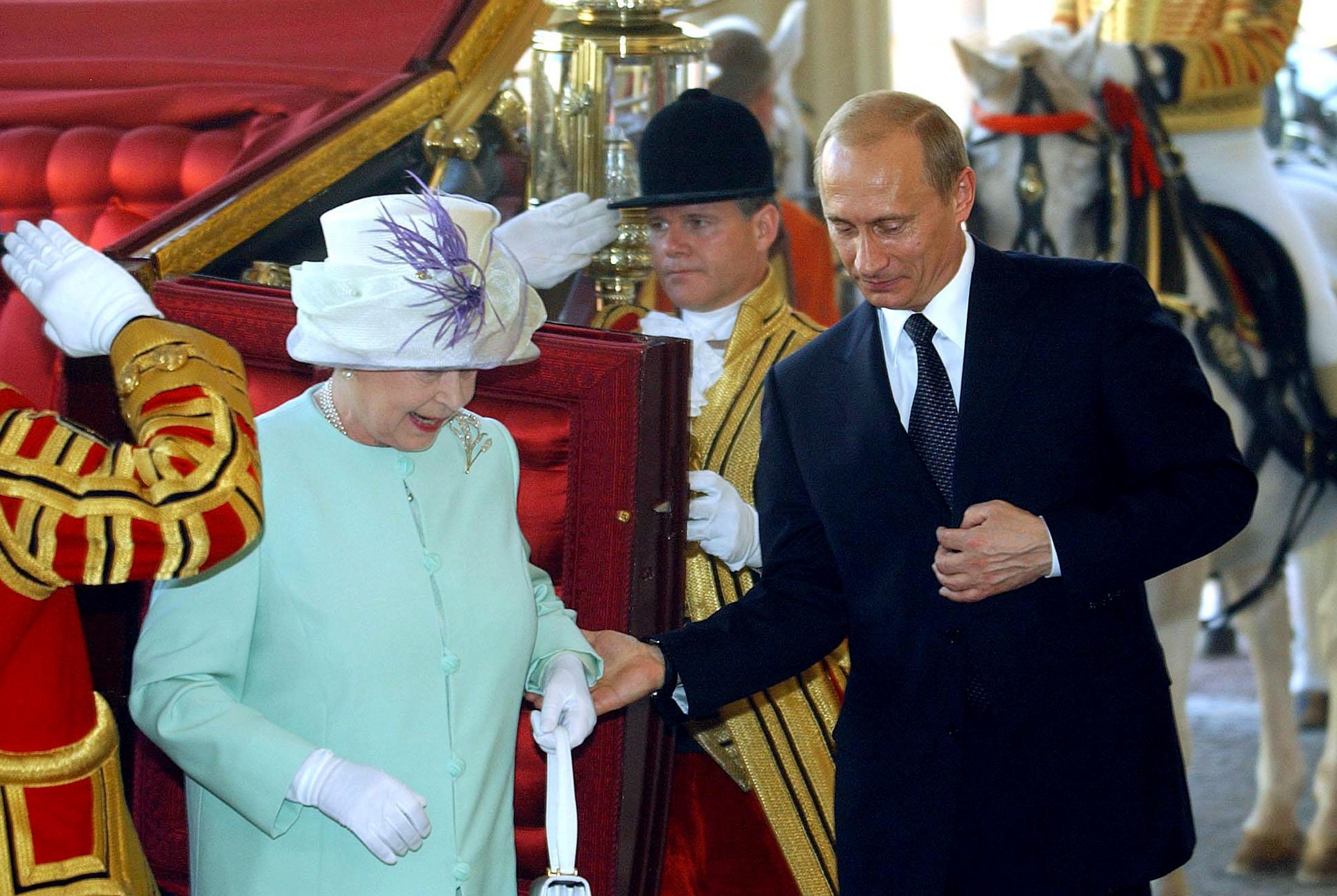 8/10. Путин током посете Лондону помаже краљици Елизабети II да изађе из кочије у Бакингемској палати.