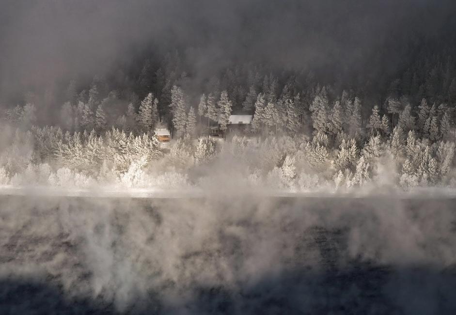 """""""Sauna"""". Snimljeno na Jeniseju pod vrlo niskim temperaturama, u okolici sela Ovsjanka. Pri ovako niskim temperaturama obično se s rijeke diže izmaglica koja od pogleda zaklanja drugu obalu. Udar vjetra oblikovao je u magli nestvaran """"prozor"""" obavijen bijelom tišinom."""