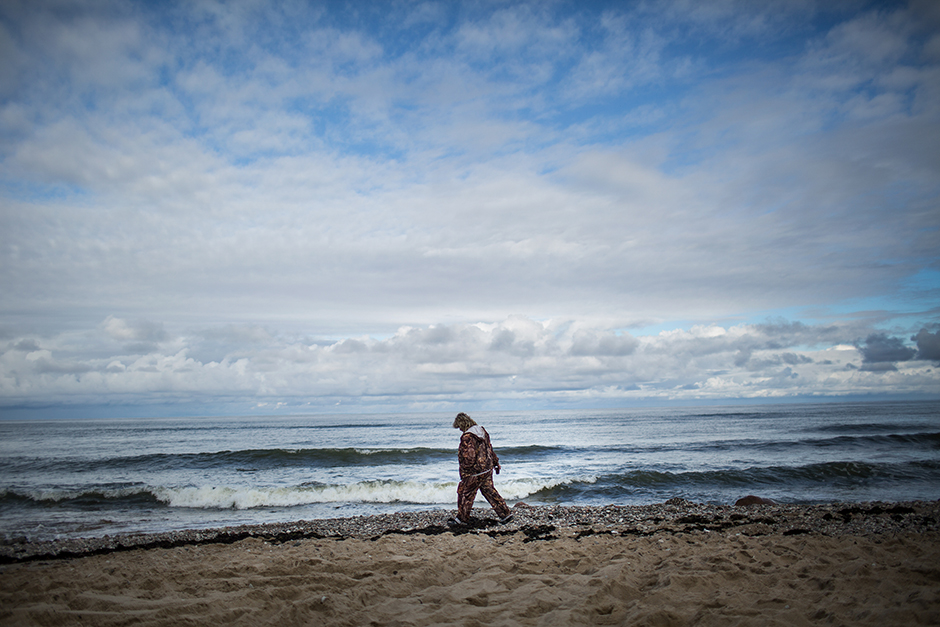 """4/15. Жена претражује морску траву на обали Балтичког мора код Калињинграда у нади да ће пронаћи бар неки мањи комад ћилибара. Ове жене – међу локалним житељима познате као """"галебови"""" – понекад наилазе и на крупне комаде веће вредности које море избаци на обалу."""