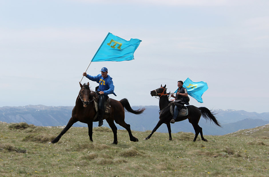 Young Tatars with the Crimean Tatars blue flags make the ascent of the Chatyr-Dag mounts massif to honor the victims of the 1944 deportation of Crimean Tatars, near Alushta, Crimea, on May 16.