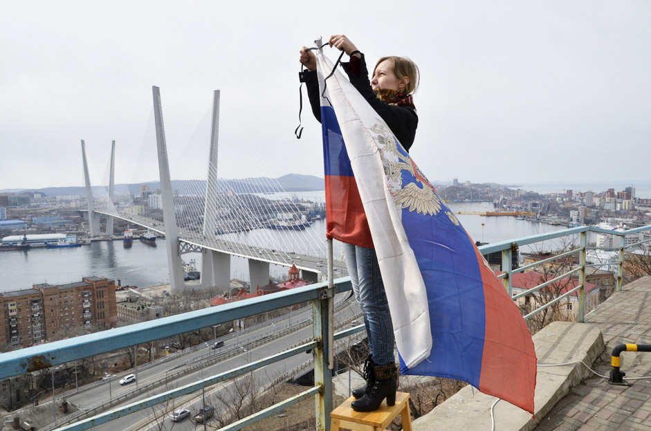 A woman attaches a black ribbon for those killed in the sinking of Dalniy Vostok, to a Russian national flag in Vladivostok April 7, 2015. A Russian trawler Dalniy Vostok sank in the Sea of Okhotsk off Russia's far eastern Kamchatka peninsula on April 2, 2015, killing at least 56 of the 132 crew, the emergencies ministry said on April 2.