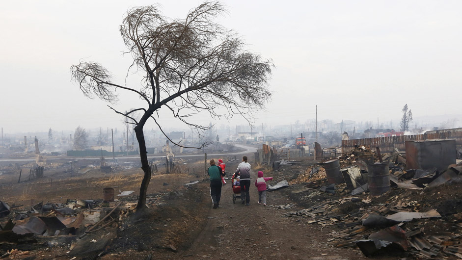 Family members walk away while passing the debris of destroyed buildings in the settlement of Shyra, damaged by recent wildfires, in Khakassia region, April 13, 2015. More than 20 villages and towns have been damaged by the fires that have been burning for several days in dry and windy weather.